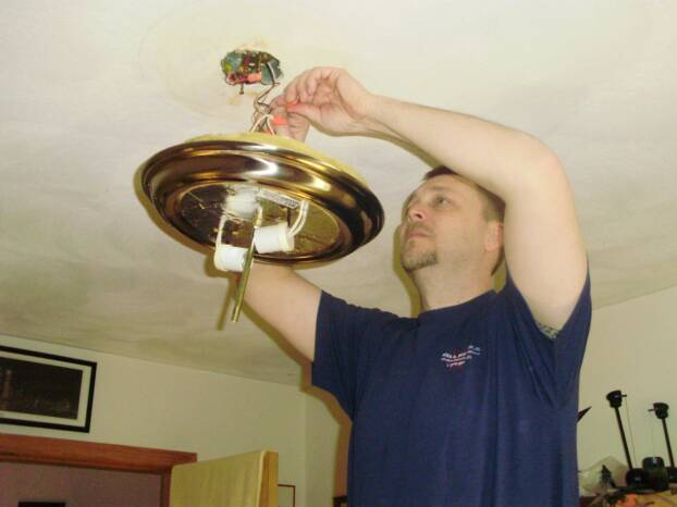A licensed electrician installing a light.